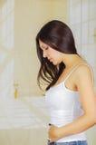 Den unga härliga latinamerikanska kvinnan som trycker på hennes buk som lider menstruations- period, smärtar, det kvinnliga vård- Fotografering för Bildbyråer