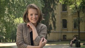 Den unga härliga lyckliga flickan är stå, och le in parkera i dag i sommar som håller ögonen på på kameran stock video