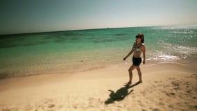 Den unga härliga lyckliga flickan kopplar av längs kusten stock video