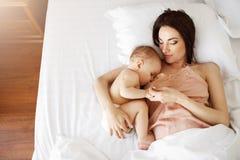 Den unga härliga mamman som ammar hennes nyfött, behandla som ett barn att ligga i säng hemma Från över Arkivbilder