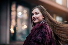 Den unga härliga modellflickan ler och ser tillbaka i staden Dynamiskt går unga flickan ner gatan Hår som fladdrar i Arkivfoton