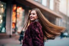 Den unga härliga modellflickan ler och ser tillbaka i staden Dynamiskt går unga flickan ner gatan Hår som fladdrar i Royaltyfri Foto