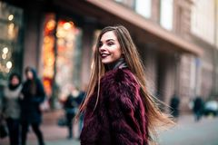 Den unga härliga modellflickan ler och ser tillbaka i staden Dynamiskt går unga flickan ner gatan Hår som fladdrar i Arkivbild