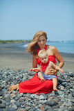 Den unga härliga modern med behandla som ett barn sonen på havsstranden arkivfoto
