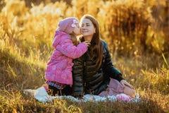 Den unga härliga modern med hennes dotter på går på en solig höstdag De sitter på en pläd på gräset, dotterkisse royaltyfri fotografi
