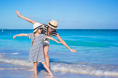 Den unga härliga modern och hennes förtjusande lilla dotter har gyckel på den tropiska stranden Fotografering för Bildbyråer