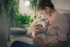Den unga härliga modern som ammar hennes nyfött, behandla som ett barn pojken Arkivfoton