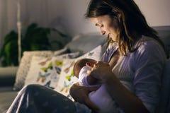 Den unga härliga modern som ammar hennes nyfött, behandla som ett barn pojken på ni Arkivbilder