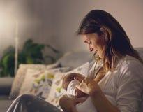 Den unga härliga modern som ammar hennes nyfött, behandla som ett barn pojken på ni Arkivfoto