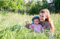 Den unga härliga modern som spelar i gräset med hennes litet, behandla som ett barn dottern i Panama Arkivfoton