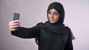 Den unga härliga muslimflickan i hijab har en video appell på smartphonen, den vinkande hälsningen, kommunikationsbegreppet, klos