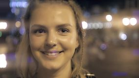 Den unga härliga nätta kvinnan som ler och poserar på stadsgatan i natten mot afton, tänder bokehbakgrund stock video