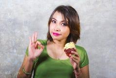 Den unga härliga och lyckliga latinamerikanska kvinnan som äter den smakliga och läckra gula söta muffin som poserar på bakgrund  arkivbilder