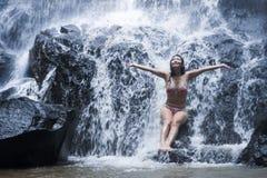 Den unga härliga och söta asiatiska kvinnan i bikinin som får kroppen den våta under-strömmen av naturligt fantastiskt vattenfall royaltyfria foton