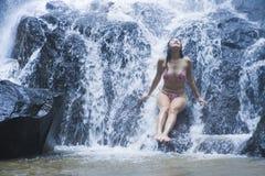Den unga härliga och söta asiatiska kvinnan i bikinin som får kroppen den våta under-strömmen av naturligt fantastiskt vattenfall fotografering för bildbyråer