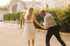 Den unga härliga parmaken i en vit skjorta och en kvinna i en klänning som går runt om, parkerar i sommartid arkivbild