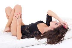 Den unga härliga sexiga charmiga kvinnan snör åt in damunderkläderbodysuiten ly Arkivfoto