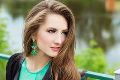 Den unga härliga sexiga flickan i en grön klänning med härlig makeup med gräsplan fjättrar sammanträde på flodbanken i staden Royaltyfria Bilder