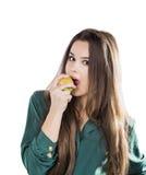 Den unga härliga sexiga flickan med mörkt lockigt hår som rymmer det stora äpplet för att tycka om smaken och, bantar, leendet Royaltyfri Foto