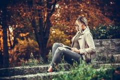 Den unga härliga stads- kvinnan är läseboken, medan sitta i Royaltyfria Foton