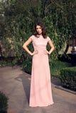 Den unga härliga stilfulla flickan som poserar i långa rosa färger, klär Arkivfoton