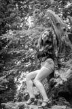 Den unga härliga tonåringflickan med långt hår i en skjorta och en grov bomullstvill kortsluter att vila på ett träd under en gå  Arkivfoto