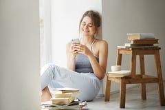 Den unga härliga tonårs- flickan som surfar rengöringsduken som ser telefonskärmen som ler sammanträde på golv bland gamla böcker Royaltyfri Fotografi