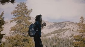 Den unga härliga turist- flickan med ryggsäcken tar foto av att förbluffa vit vaggar på Yosemite nationalparkultrarapid stock video