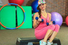Den unga härliga vita flickan i en rosa sportdräkt gör fysiska övningar med hantlar på konditionmitten royaltyfri foto