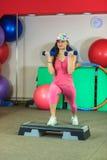Den unga härliga vita flickan i en rosa sportdräkt gör fysiska övningar med hantlar på konditionmitten royaltyfria bilder