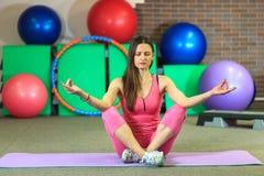 Den unga härliga vita flickan i en rosa sportdräkt mediterar på yogagruppen på konditionmitten royaltyfria bilder