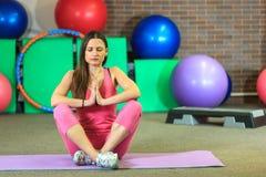 Den unga härliga vita flickan i en rosa sportdräkt mediterar på yogagruppen på konditionmitten royaltyfri fotografi