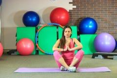 Den unga härliga vita flickan i en rosa sportdräkt mediterar på yogagruppen på konditionmitten royaltyfria foton