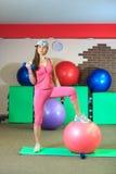 Den unga härliga vita flickan i lock och rosa färgsportdräkt gör fysiska övningar med dumbells och passformbollen på konditionmit royaltyfria foton