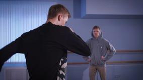 Den unga höft-flygtur dansaren i svart byxa och sweater deltar i breakdancestrid med hans vän svart pojke arkivfilmer