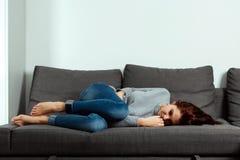 Den unga h?rliga flickan lider fr?n magekramper, och buk- sm?rta och att ligga p? en hem- soffa Begreppet av buk- sm?rtar, kvinnl arkivbild