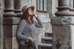 Den unga h?rliga kvinnan i hatt tar bilden med den gammalmodiga kameran, utomhus arkivfoton