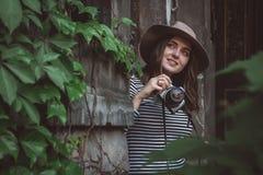 Den unga h?rliga kvinnan i hatt tar bilden med den gammalmodiga kameran, utomhus arkivbilder