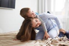 Den unga h?rliga modern och hennes ikl?dda pyjamas f?r liten son har gyckel p? s?ngen i det ljusa hemtrevliga sovrummet fotografering för bildbyråer