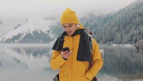 Den unga handelsresandemannen som använder smartphonen, i att fotvandra vinter, turnerar Snöig suddiga berg udde och sjö Resa och lager videofilmer