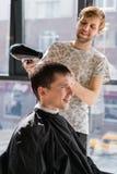 Den unga hipstergrabben i barberare shoppar, frisören som klipper hår med sax som fönar Begreppsmanställe arkivfoton