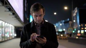 Den unga hipstergrabben som utomhus använder den moderna smartphonen, mannen som pratar med vänner på samkvämmen, knyter kontakt, arkivfilmer