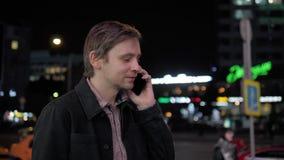 Den unga hipstergrabben som utomhus använder den moderna smartphonen, mannen som pratar med vänner på samkvämmen, knyter kontakt, lager videofilmer