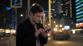 Den unga hipstergrabben som utomhus använder den moderna smartphonen, mannen som pratar med vänner på samkvämmen, knyter kontakt, stock video