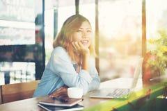 Den unga hipsterkvinnan vilar en hand på hakan, och leendet tycker om i caf royaltyfria foton