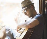 Den unga hipstermannen spelar gitarren Fotografering för Bildbyråer