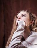 Den unga härliga blonda flickan är ledsen Arkivfoto