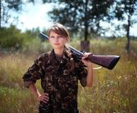 Den unga härliga flickan med en hagelgevär ser in i avståndet Arkivbild