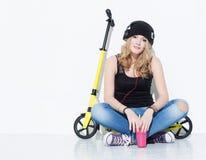 Den unga härliga gladlynta modeflickan i jeans, gymnastikskor, hatt sitter på en gul sparkcykel och att lyssna till musik på hörl Royaltyfri Fotografi