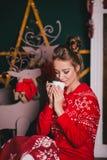 Den unga härliga kvinnan i röd varm pyjamas med scandinavianen smyckar att sitta nära den dekorativa spisen och att dricka varm k Arkivbild
